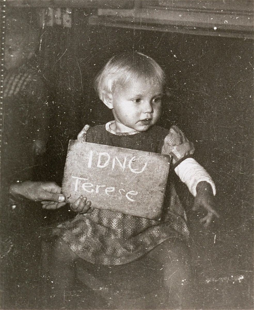 Terese Idnu poses with a name card intended to help any of her surviving family members locate her at the Kloster Indersdorf DP camp.  This photograph was published in newspapers to facilitate reuniting the family.