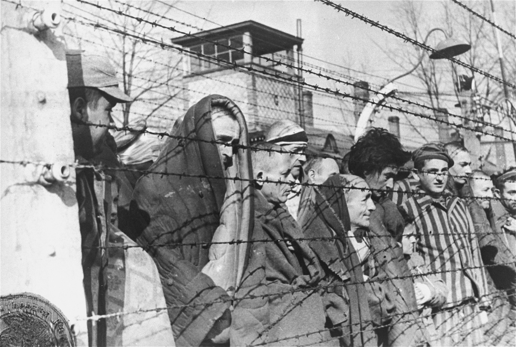 Survivors of Auschwitz peer through the barbed wire of the camp.  STILL PHOTOGRAPH FROM THE SOVIET FILM of the liberation of Auschwitz, taken by the film unit of the First Ukrainian Front.