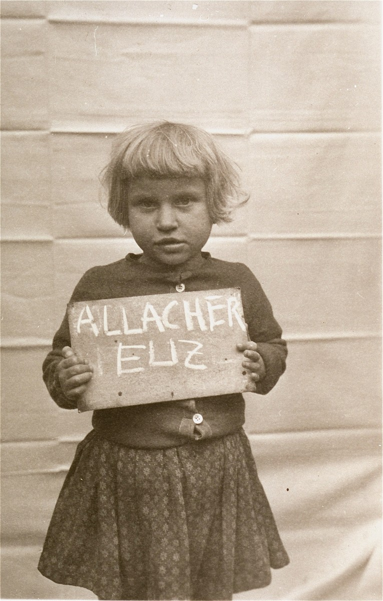 Eliz Allacher holds a name card intended to help any of her surviving family members locate her at the Kloster Indersdorf DP camp.  This photograph was published in newspapers to facilitate reuniting the family.