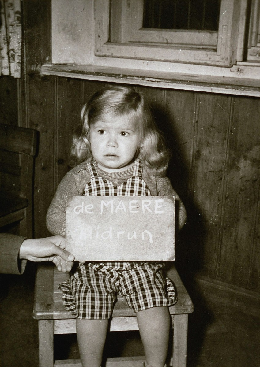 Toddler Hidrun de Maere poses with a name card intended to help any of her surviving family members locate her at the Kloster Indersdorf DP camp.  This photograph was published in newspapers to facilitate reuniting the family.