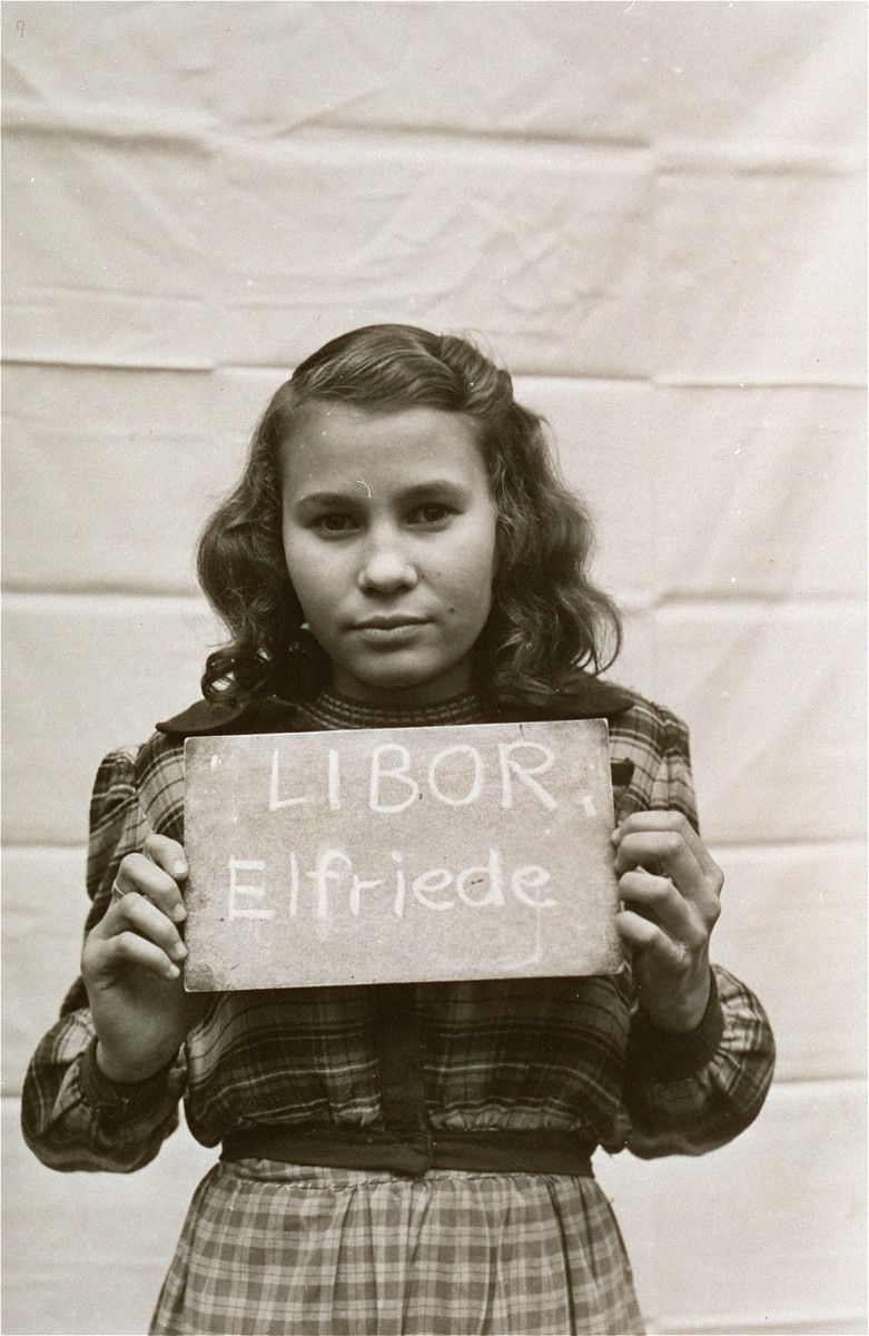 Elfriede Libor holds a name card intended to help any of her surviving family members locate her at the Kloster Indersdorf DP camp.  This photograph was published in newspapers to facilitate reuniting the family.