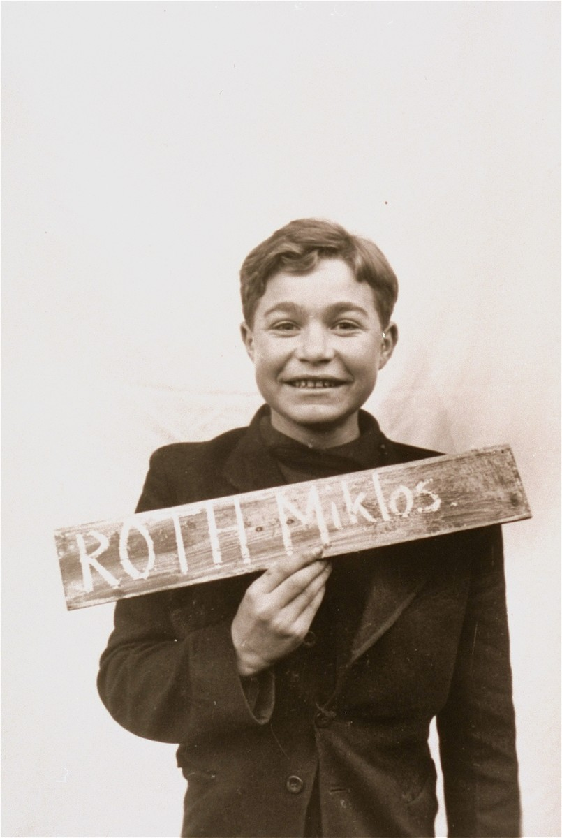 Miklos Roth holds a name card intended to help any of his surviving family members locate him at the Kloster Indersdorf DP camp.  This photograph was published in newspapers to facilitate reuniting the family.