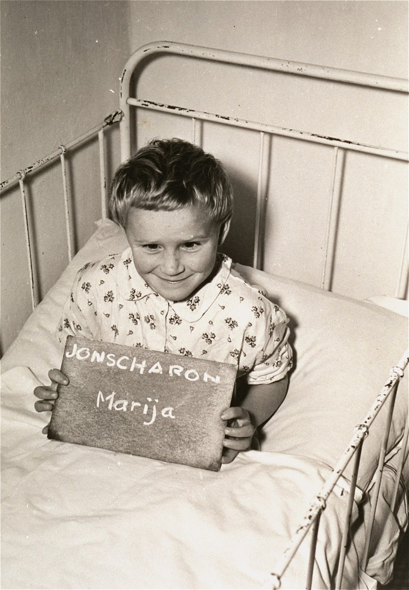 Marija Jonscharon holds a name card intended to help any of her surviving family members locate her at the Kloster Indersdorf DP camp.  This photograph was published in newspapers to facilitate reuniting the family.