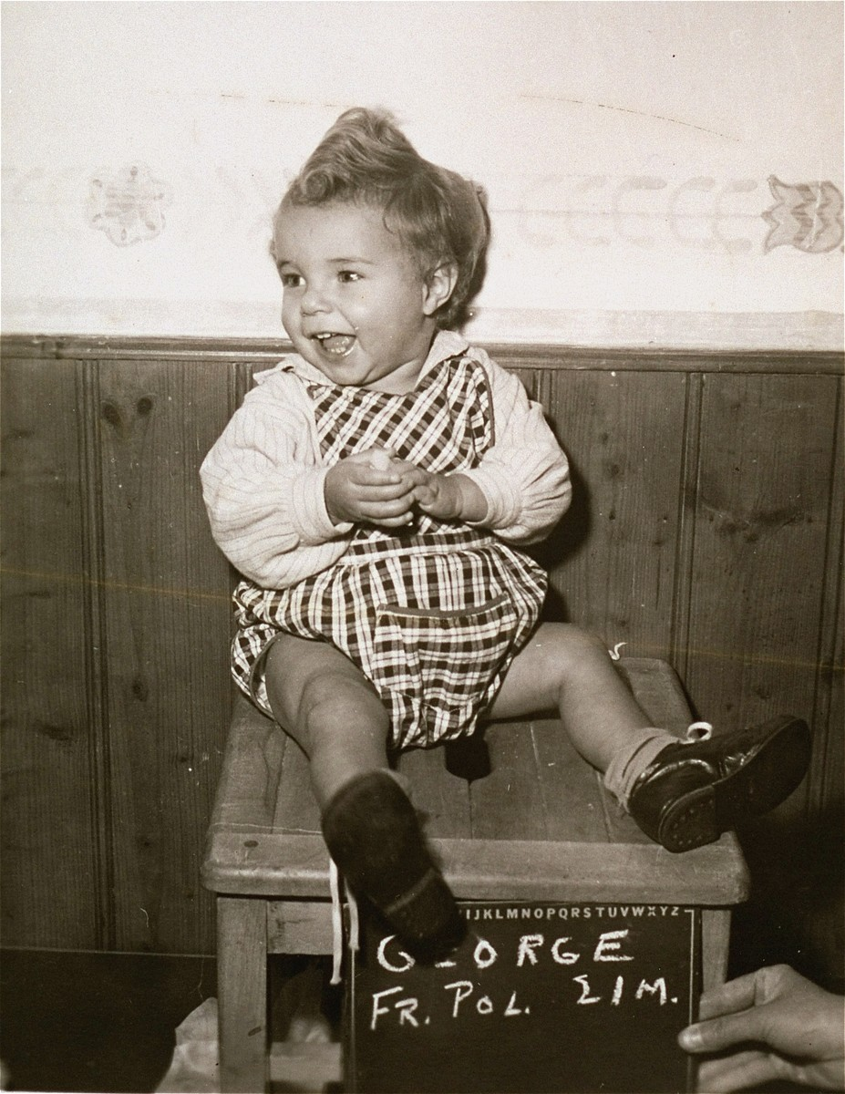Polish toddler George, surname unknown, with a name card intended to help any of his surviving family members locate him at the Kloster Indersdorf DP camp.  This photograph was published in newspapers to facilitate reuniting the family.