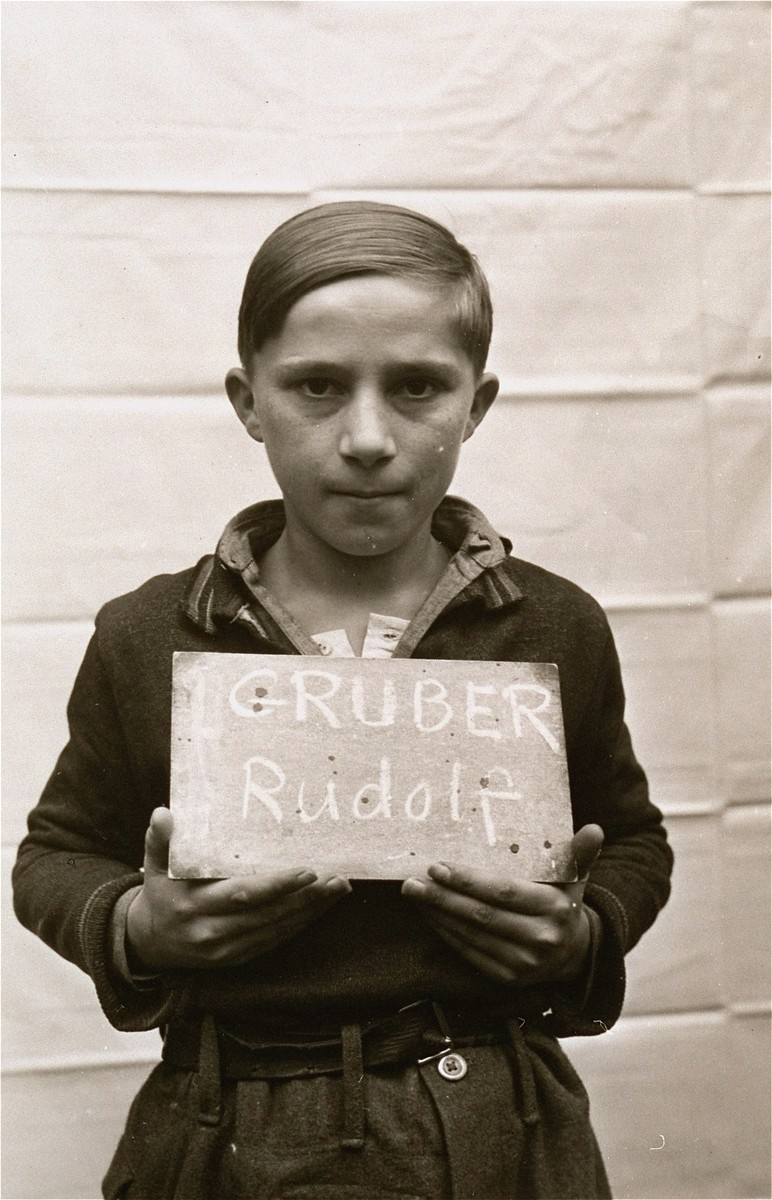 Rudolf Gruber holds a name card intended to help any of his surviving family members locate him at the Kloster Indersdorf DP camp.  This photograph was published in newspapers to facilitate reuniting the family.