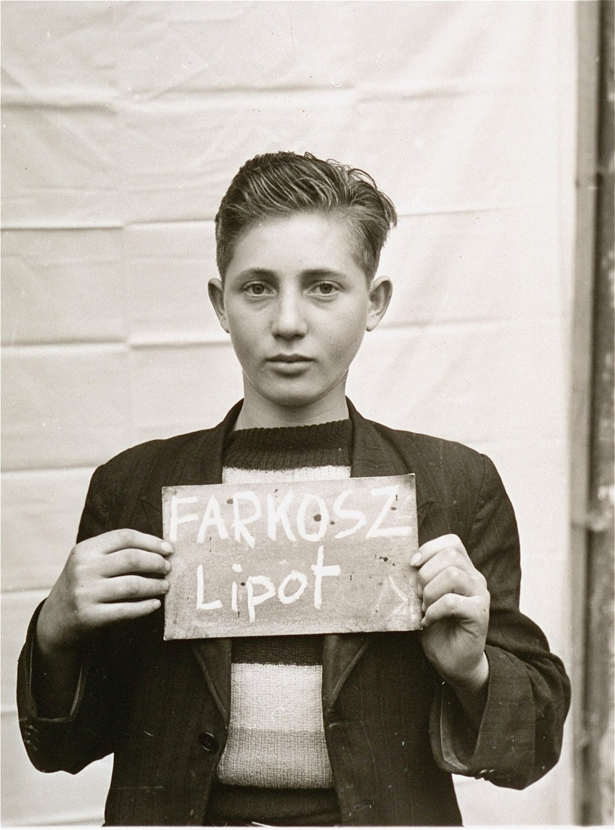 Lipot Farkosz holds a name card intended to help any of his surviving family members locate him at the Kloster Indersdorf DP camp.  This photograph was published in newspapers to facilitate reuniting the family.