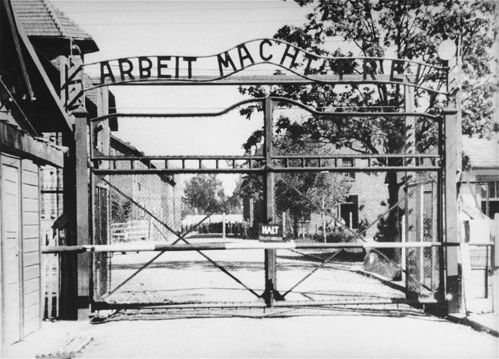 """View of the entrance to the main camp of Auschwitz (Auschwitz I).  The gate bears the motto """"Arbeit Macht Frei"""" (Work makes one free)."""
