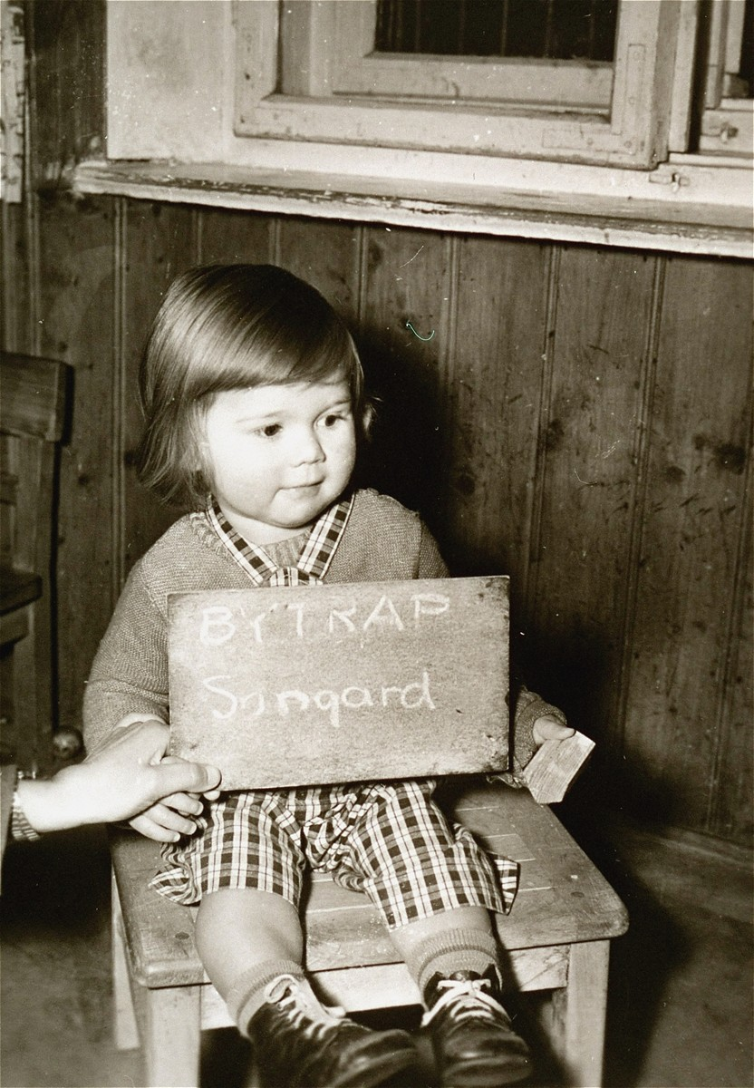 Songard Bytrap with a name card intended to help any of her surviving family members locate her at the Kloster Indersdorf DP camp.  This photograph was published in newspapers to facilitate reuniting the family.