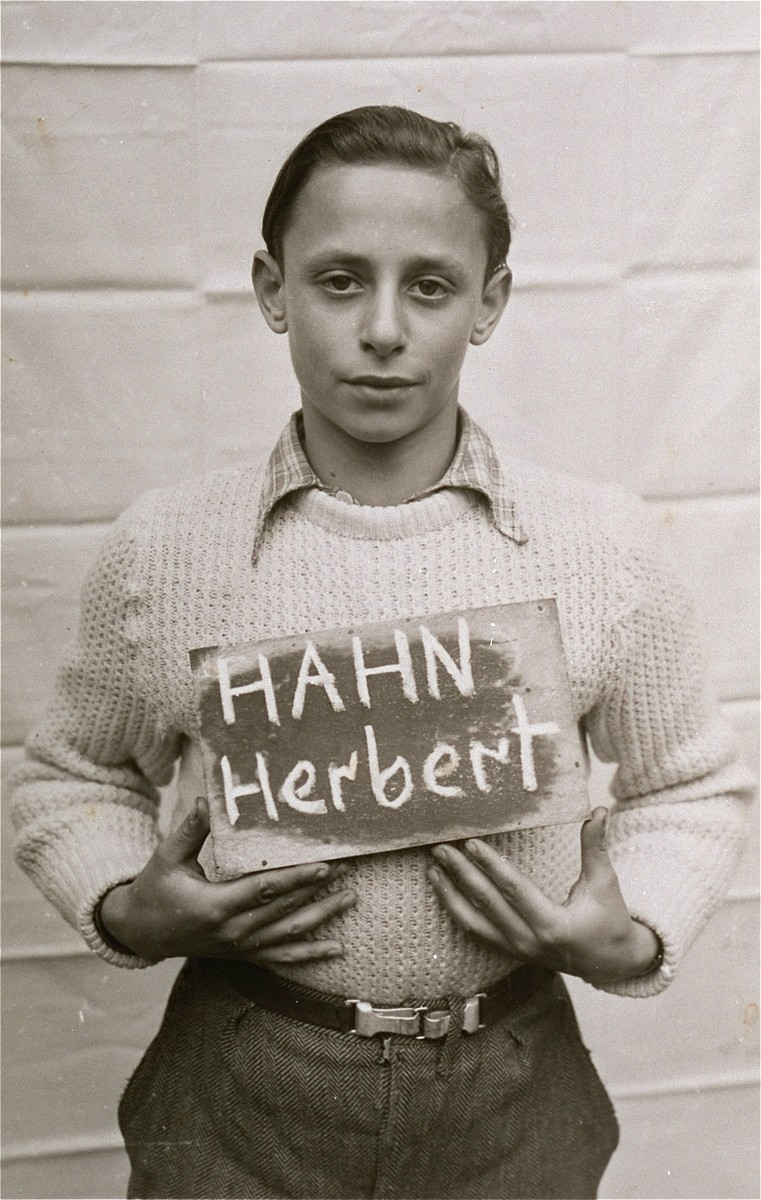 Herbert Hahn holds a name card intended to help any of his surviving family members locate him at the Kloster Indersdorf DP camp.  This photograph was published in newspapers to facilitate reuniting the family.