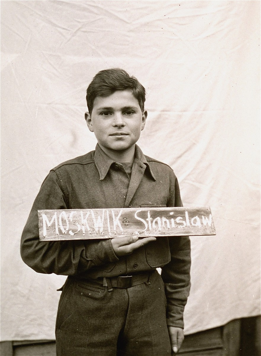 Stanislaw Moskwik holds a name card intended to help any of his surviving family members locate him at the Kloster Indersdorf DP camp.  This photograph was published in newspapers to facilitate reuniting the family.