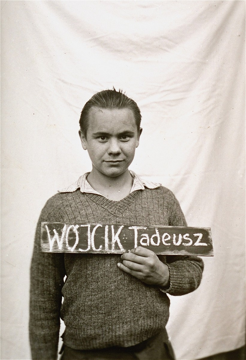 Tadeusz Wojcik holds a name card intended to help any of his surviving family members locate him at the Kloster Indersdorf DP camp.  This photograph was published in newspapers to facilitate reuniting the family.
