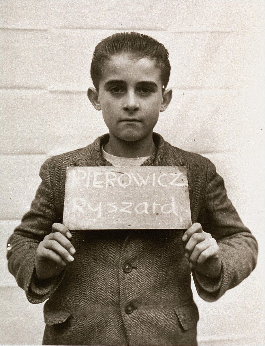 Ryszard Pierowicz holds a name card intended to help any of his surviving family members locate him at the Kloster Indersdorf DP camp.  This photograph was published in newspapers to facilitate reuniting the family.