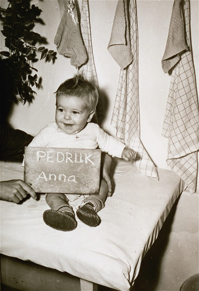 Infant Anna Pedruk with a name card intended to help any of her surviving family members locate her at the Kloster Indersdorf DP camp.  This photograph was published in newspapers to facilitate reuniting the family.