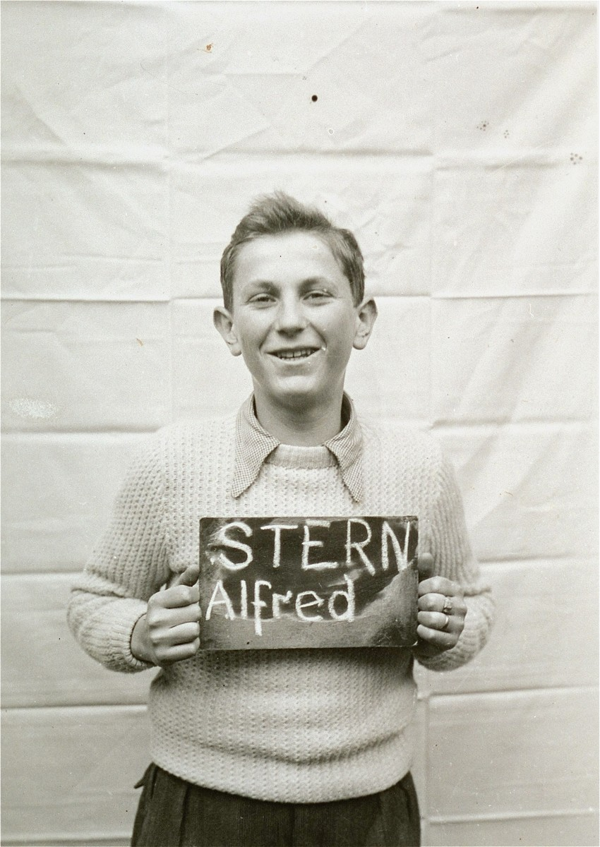 Alfred Stern holds a name card intended to help any of his surviving family members locate him at the Kloster Indersdorf DP camp.  This photograph was published in newspapers to facilitate reuniting the family.