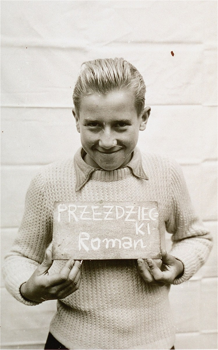 Roman Przezdziecki holds a name card intended to help any of his surviving family members locate him at the Kloster Indersdorf DP camp.  This photograph was published in newspapers to facilitate reuniting the family.