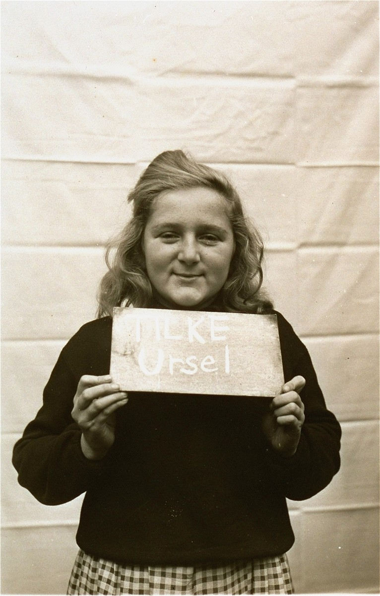 Ursel Tilke holds a name card intended to help any of her surviving family members locate her at the Kloster Indersdorf DP camp.  This photograph was published in newspapers to facilitate reuniting the family.