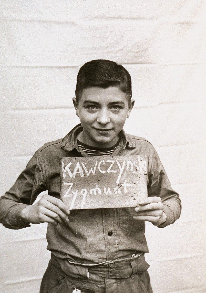 Zygmunt Kawczynski holds a name card intended to help any of his surviving family members locate him at the Kloster Indersdorf DP camp.  This photograph was published in newspapers to facilitate reuniting the family.