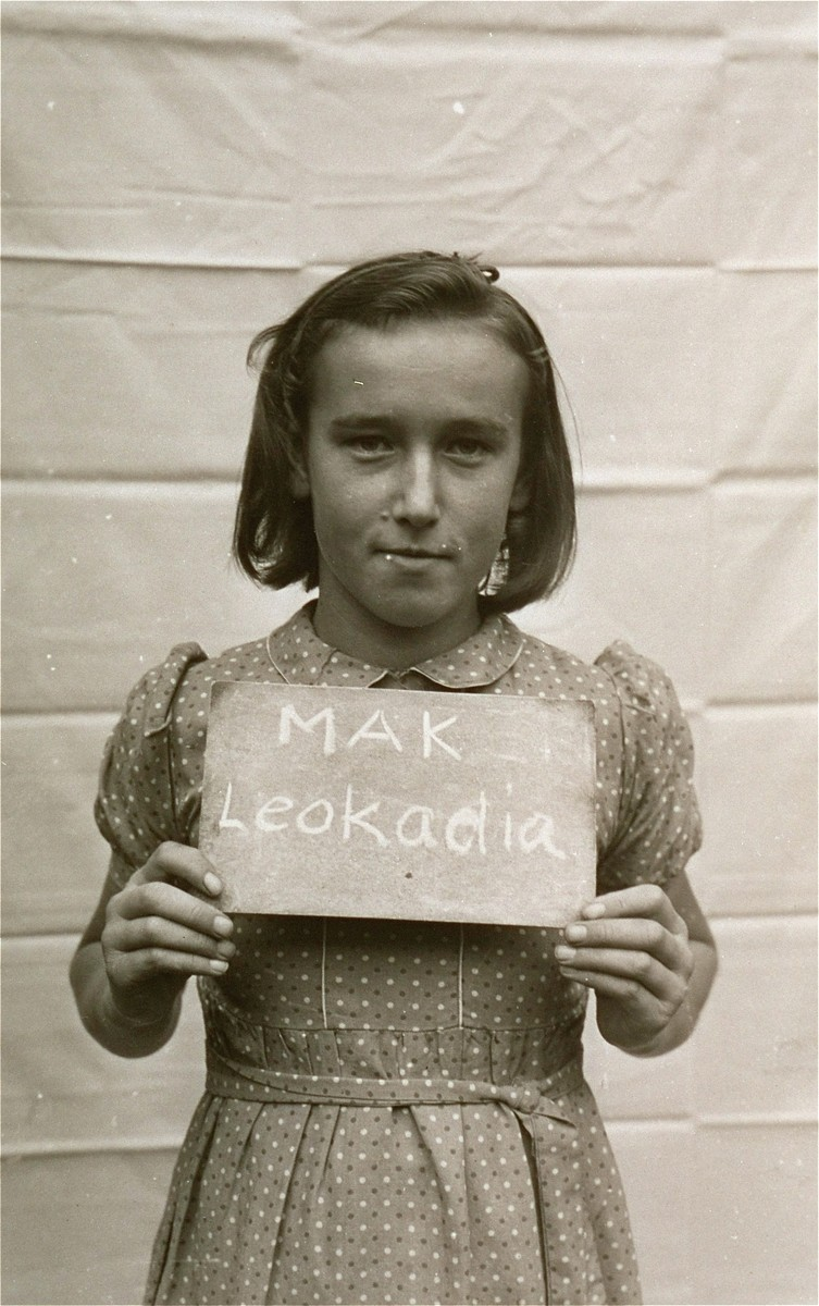 Leokadia Mak holds a name card intended to help any of her surviving family members locate her at the Kloster Indersdorf DP camp.  This photograph was published in newspapers to facilitate reuniting the family.
