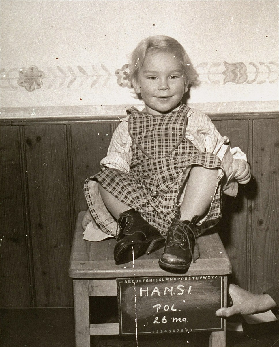 Polish child Hansi, surname unknown, poses with a name card intended to help any of her surviving family members locate her at the Kloster Indersdorf DP camp.  This photograph was published in newspapers to facilitate reuniting the family.