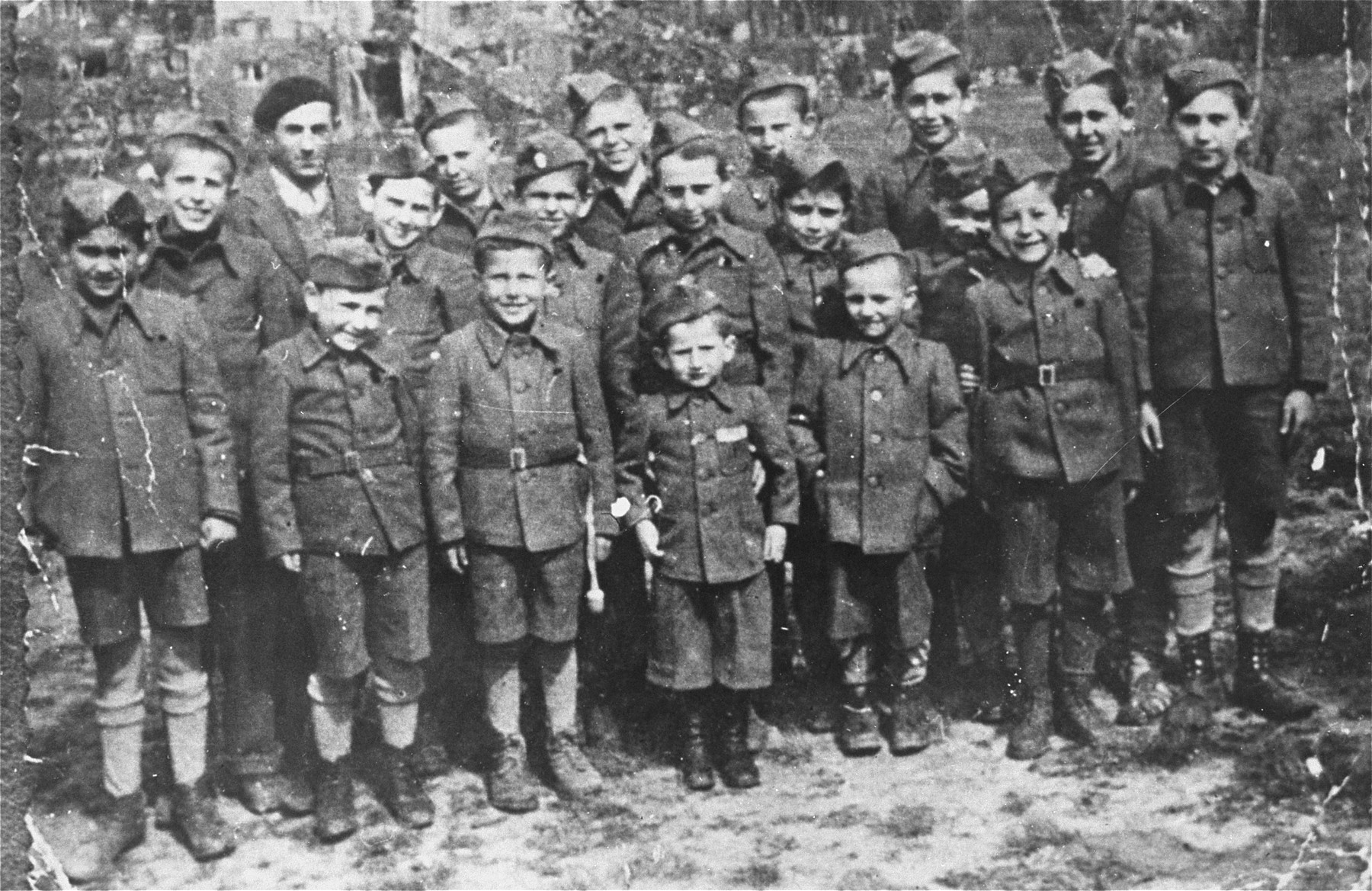 Group portrait of child survivors of the Buchenwald concentration camp.    The boys are dressed in outfits made from German uniforms due to a clothing shortage.  Among those pictured are first row (left to right): Lolek Blum, David Perlmutter, Birenbaum, Joseph Schleifstein,  unidentified, and Israel Meir Lau (middle row, far right).  Middle row: Nathan Szwarc, Jack Neeman, Berek Silber, Jacques Finkel, unidentified, Marek Milstein, and Salek Finkelsztein.  Back row: Elek Grinbaum [or Grinberg], Chaim Finkelstajn [or Charles Finkel], Romek Wekselman [or Wajsman], and Abram Czapnik.