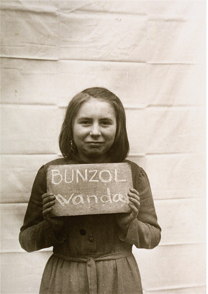 Wanda Bunzol holds a name card intended to help any of her surviving family members locate her at the Kloster Indersdorf DP camp.  This photograph was published in newspapers to facilitate reuniting the family.   She was from Upper Silesia.  Her German teacher brought her class to Bavaria to escape Soviet troops.