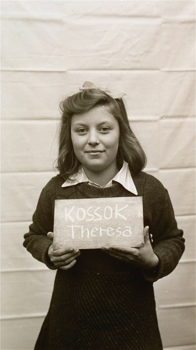 Theresa Kossok holds a name card intended to help any of her surviving family members locate her at the Kloster Indersdorf DP camp.  This photograph was published in newspapers to facilitate reuniting the family.