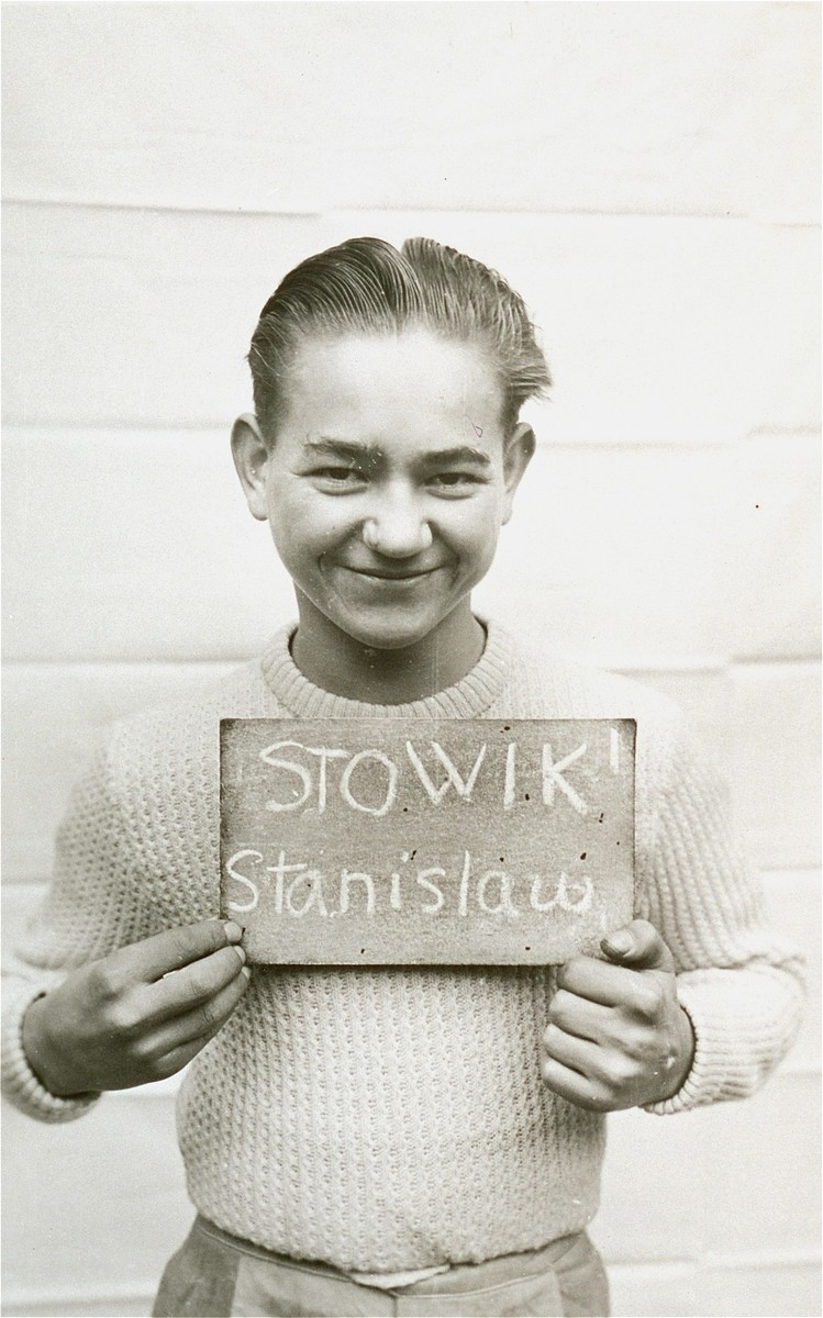 Stanislaw Stowik holds a name card intended to help any of his surviving family members locate him at the Kloster Indersdorf DP camp.  This photograph was published in newspapers to facilitate reuniting the family.