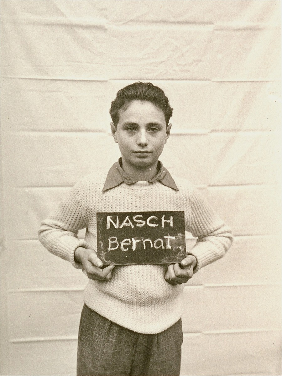 Bernat Nasch holds a name card intended to help any of his surviving family members locate him at the Kloster Indersdorf DP camp.  This photograph was published in newspapers to facilitate reuniting the family.