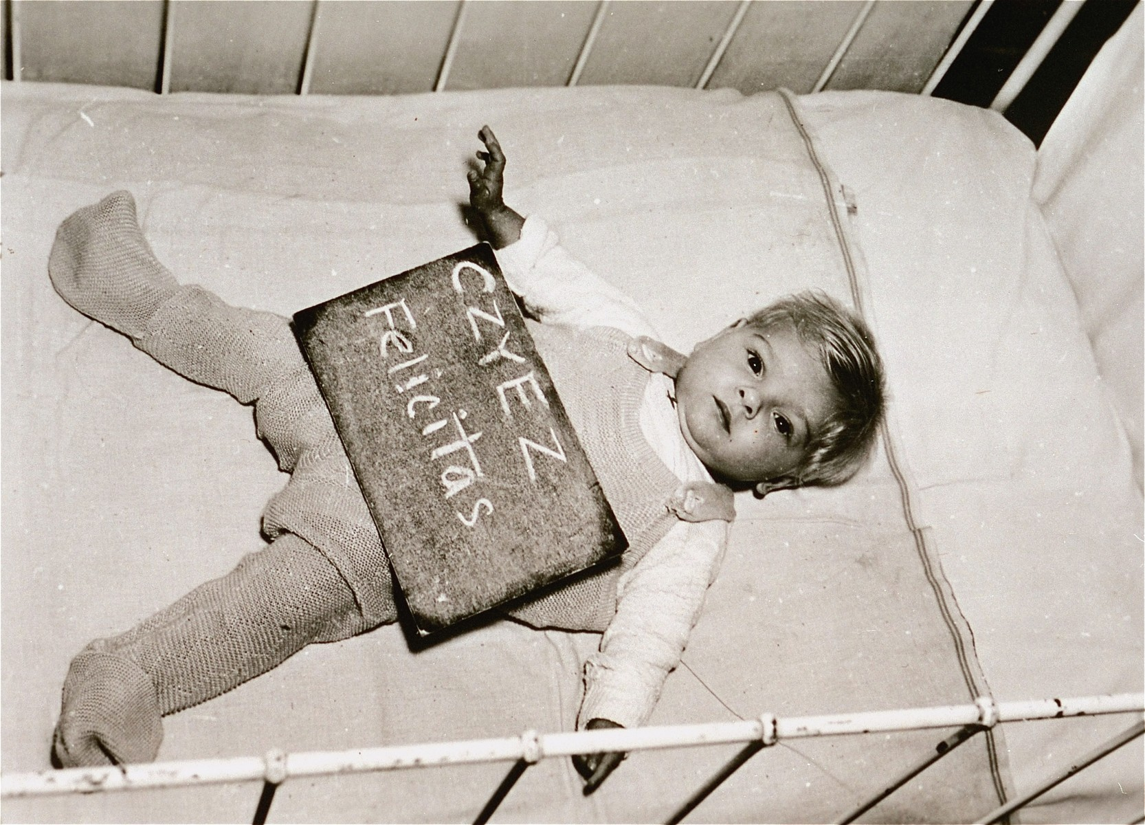 Infant Felicitas Czyez with a name card intended to help any of her surviving family members locate her at the Kloster Indersdorf DP camp.  This photograph was published in newspapers to facilitate reuniting the family.
