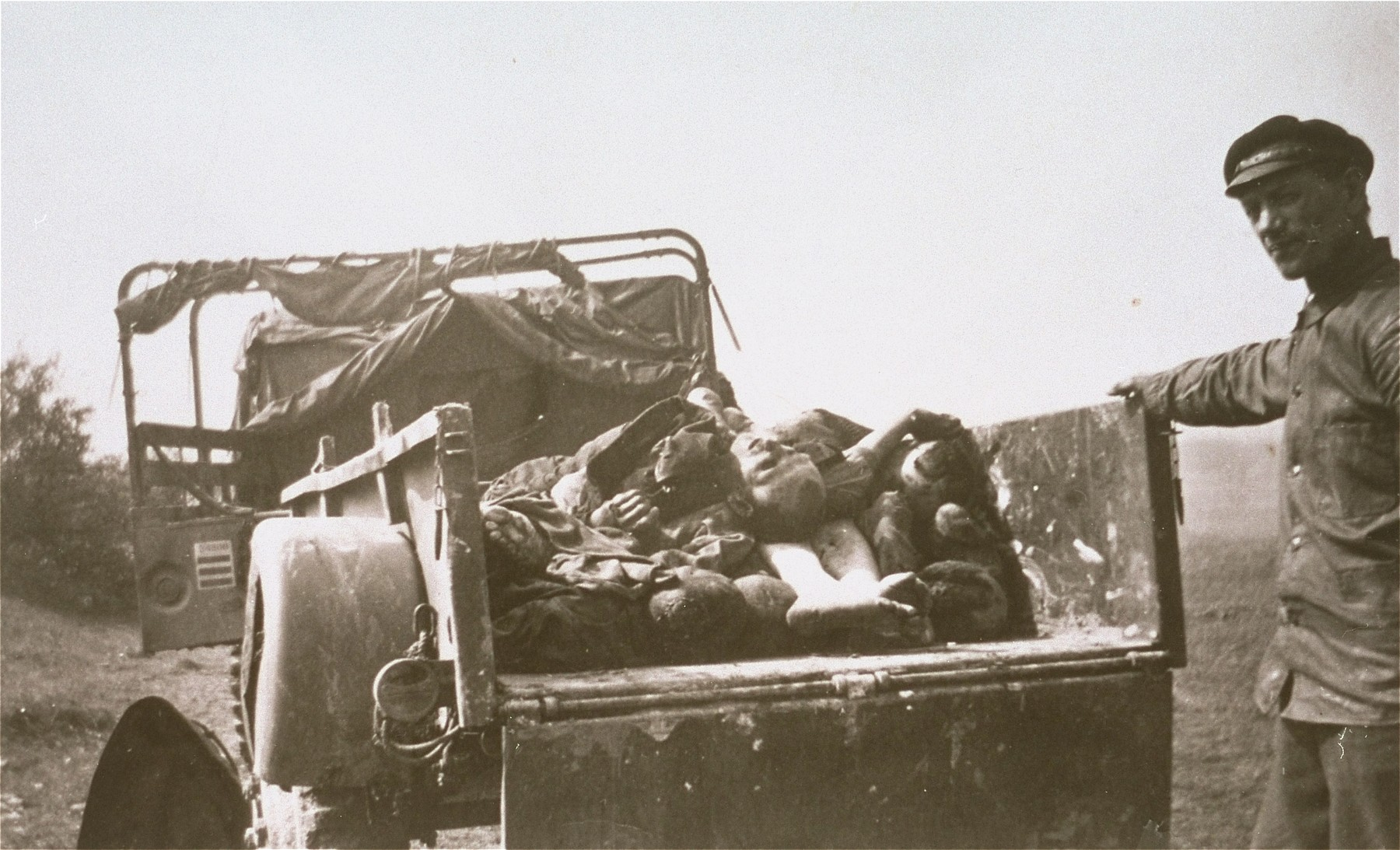 A German civilian stands beside a cart laden with the bodies of prisoners killed in Ohrdruf.