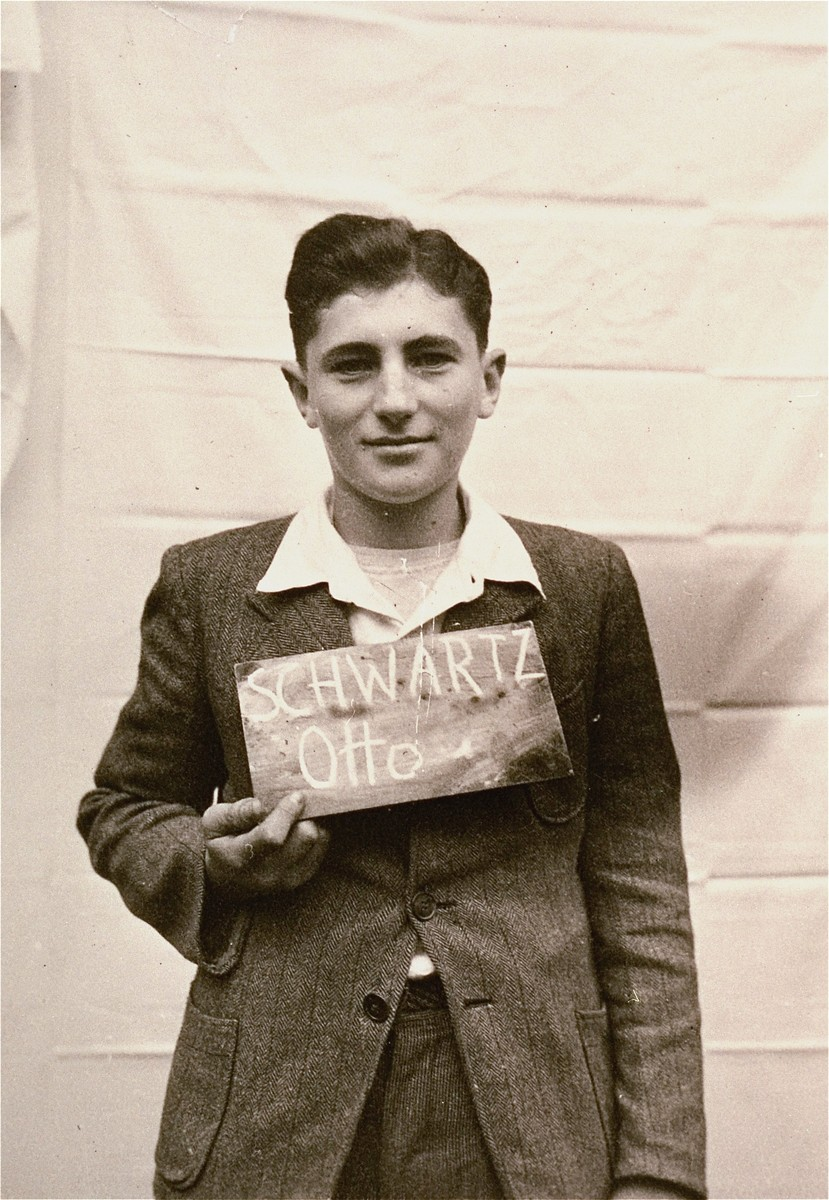 Otto Schwartz holds a name card intended to help any of his surviving family members locate him at the Kloster Indersdorf DP camp.  This photograph was published in newspapers to facilitate reuniting the family.