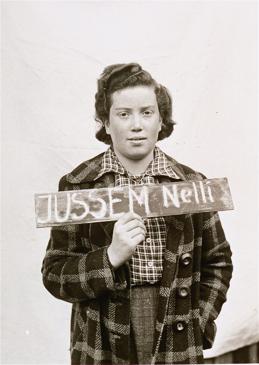 Nelli Jussem holds a name card intended to help any of her surviving family members locate her at the Kloster Indersdorf DP camp.  This photograph was published in newspapers to facilitate reuniting the family.