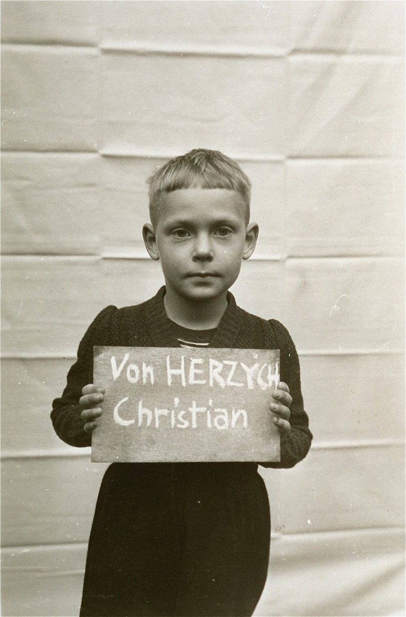 Christian von Herzych holds a name card intended to help any of his surviving family members locate him at the Kloster Indersdorf DP camp.  This photograph was published in newspapers to facilitate reuniting the family.