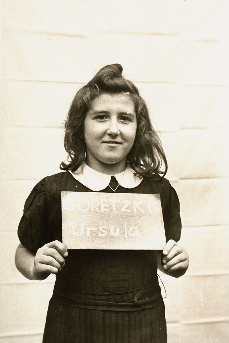 Ursula Goretski holds a name card intended to help any of her surviving family members locate her at the Kloster Indersdorf DP camp.  This photograph was published in newspapers to facilitate reuniting the family.