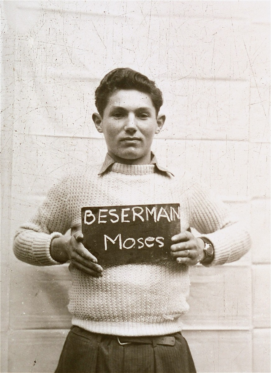 Moses Beserman holds a name card intended to help any of his surviving family members locate him at the Kloster Indersdorf DP camp.  This photograph was published in newspapers to facilitate reuniting the family.
