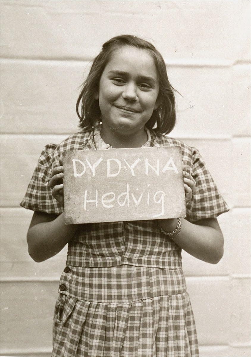 Hedvig Dydyna holds a name card intended to help any of her surviving family members locate her at the Kloster Indersdorf DP camp.  This photograph was published in newspapers to facilitate reuniting the family.