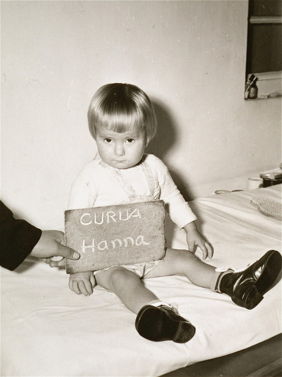 Hanna Curua with a name card intended to help any of her surviving family members locate her at the Kloster Indersdorf DP camp.  This photograph was published in newspapers to facilitate reuniting the family.