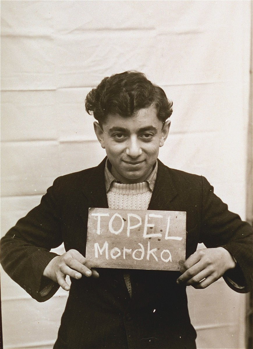 Mordka Topel holds a name card intended to help any of his surviving family members locate him at the Kloster Indersdorf DP camp.  This photograph was published in newspapers to facilitate reuniting the family.