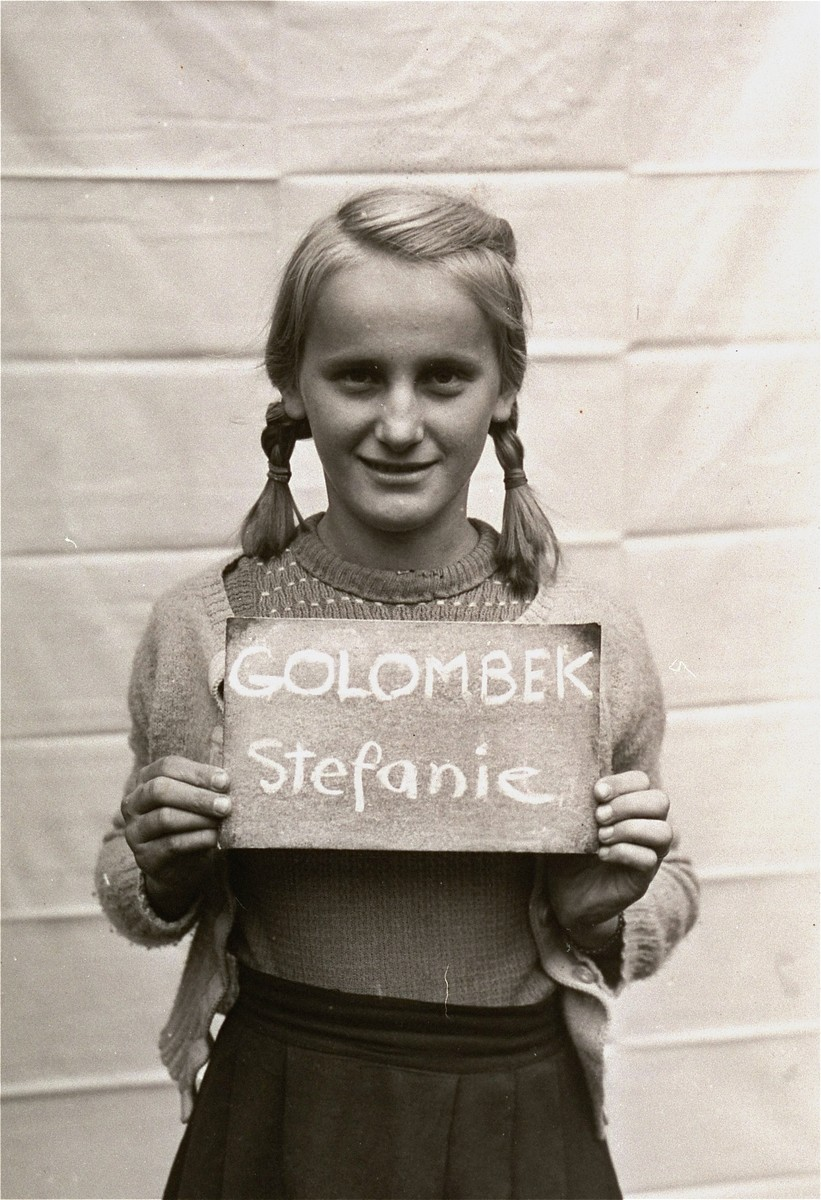 Stefanie Golombek holds a name card intended to help any of her surviving family members locate her at the Kloster Indersdorf DP camp.  This photograph was published in newspapers to facilitate reuniting the family.