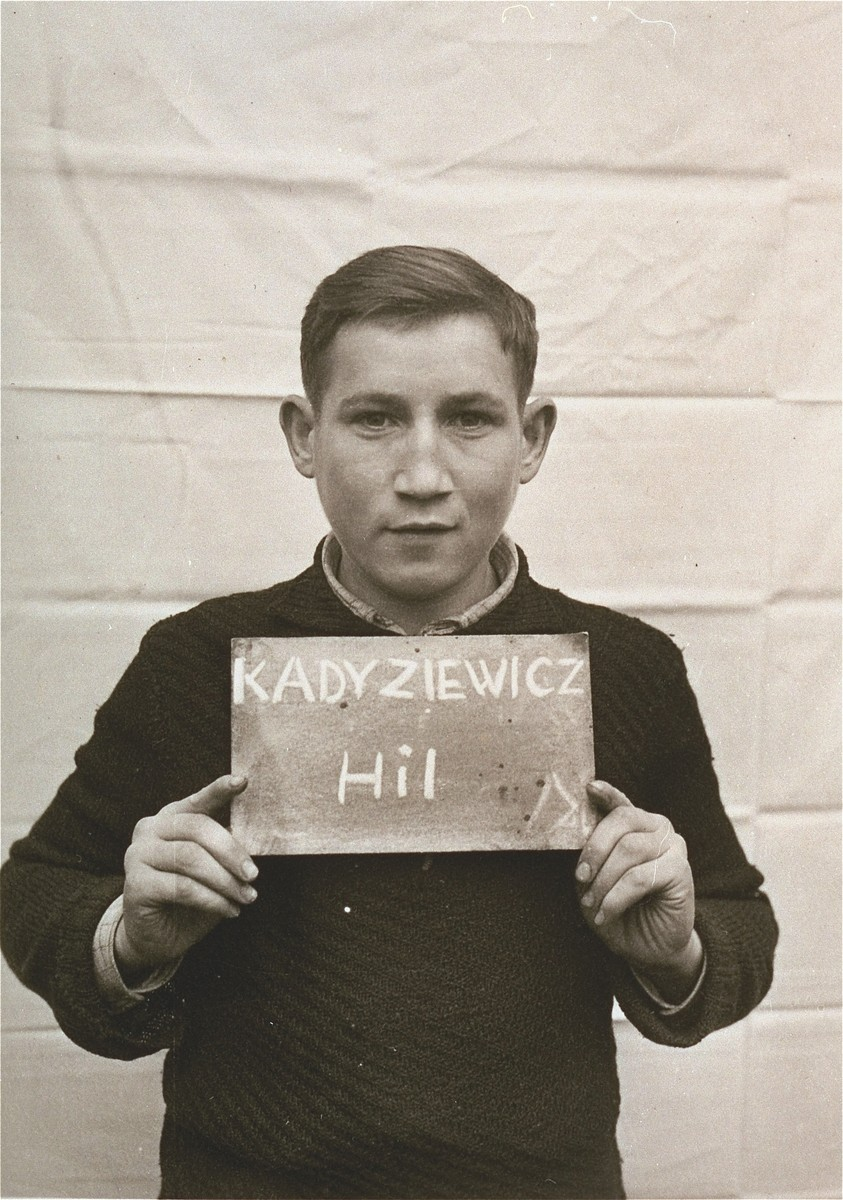 Hil Kadyziewicz holds a name card intended to help any of his surviving family members locate him at the Kloster Indersdorf DP camp.  This photograph was published in newspapers to facilitate reuniting the family.