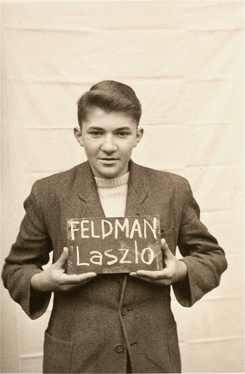 Laszlo Feldman holds a name card intended to help any of his surviving family members locate him at the Kloster Indersdorf DP camp.  This photograph was published in newspapers to facilitate reuniting the family.