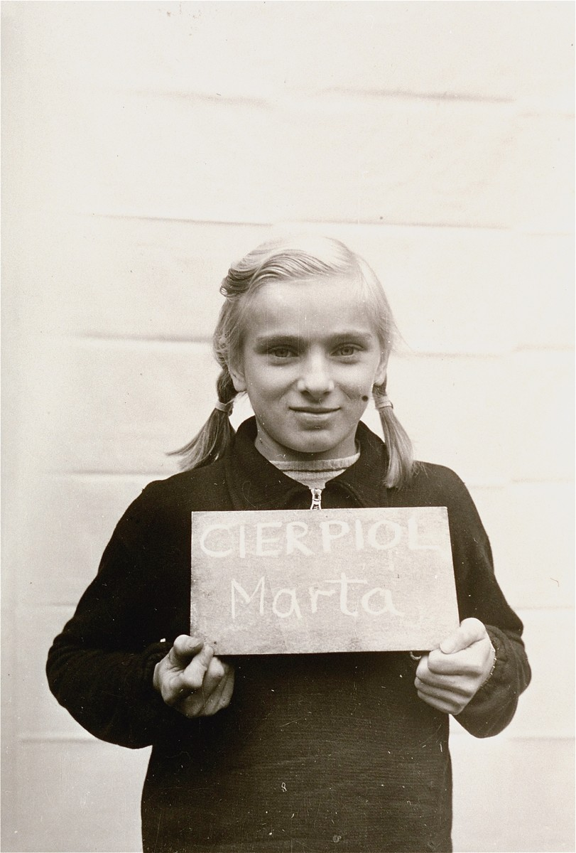 Marta Cierpiol holds a name card intended to help any of her surviving family members locate her at the Kloster Indersdorf DP camp.  This photograph was published in newspapers to facilitate reuniting the family.
