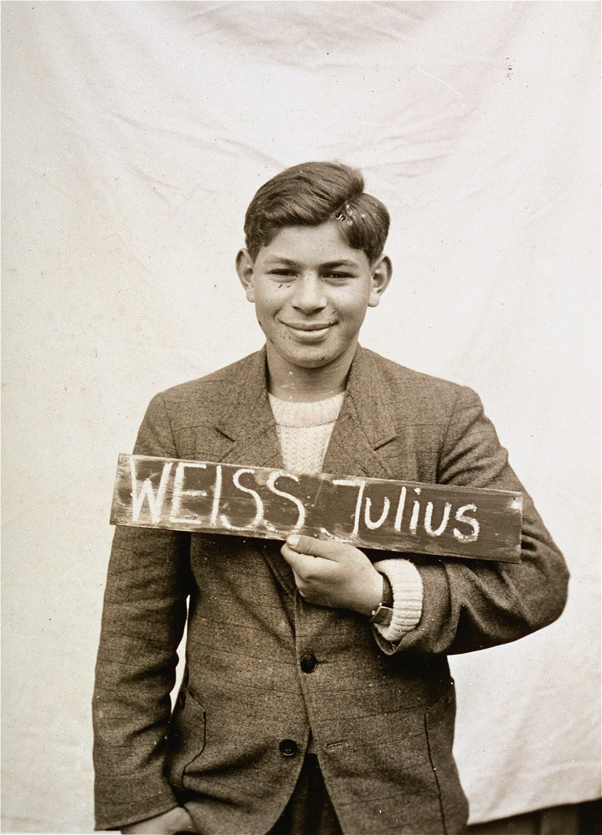 Julius Weiss holds a name card intended to help any of his surviving family members locate him at the Kloster Indersdorf DP camp.  This photograph was published in newspapers to facilitate reuniting the family.