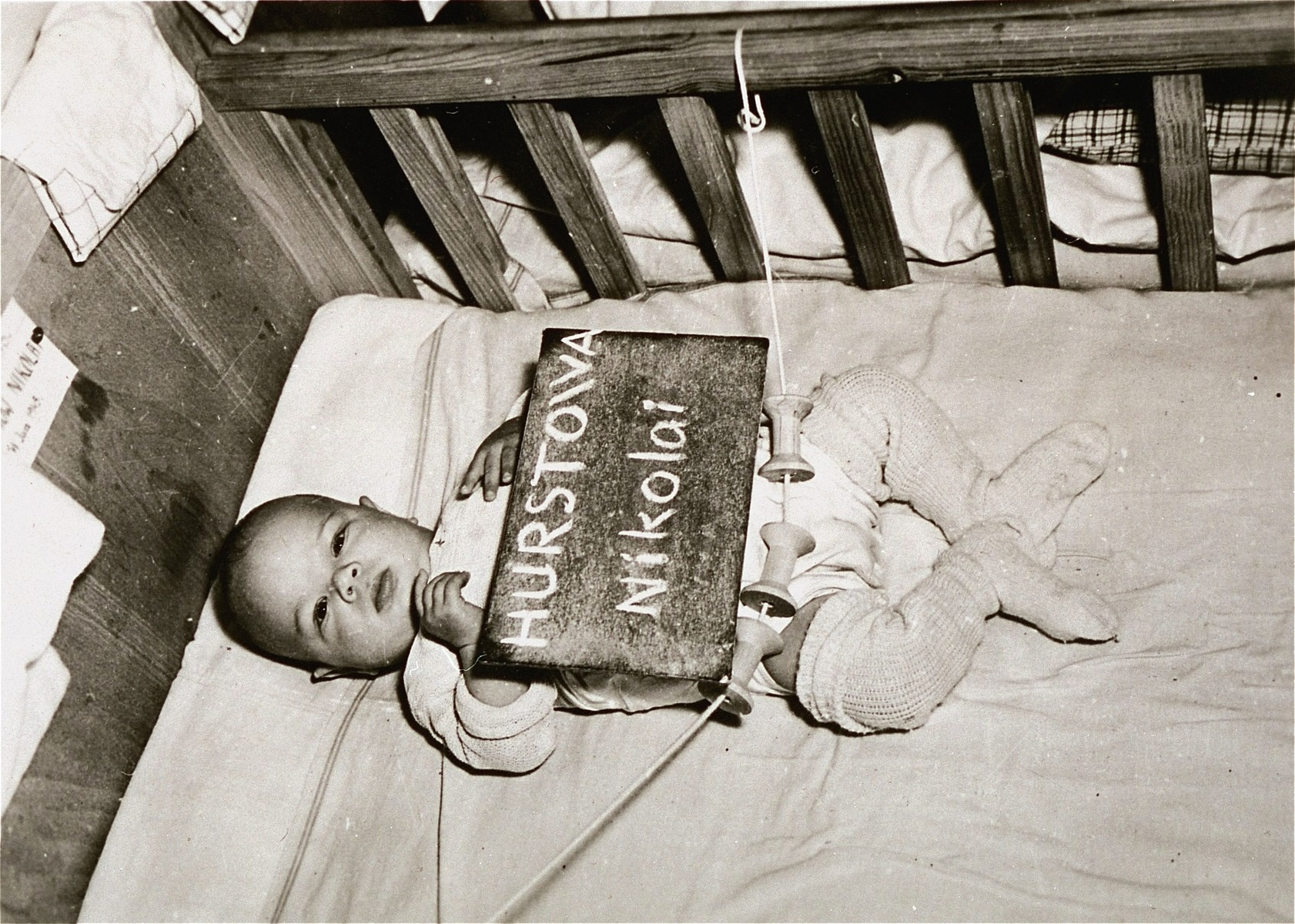 Infant Nikolai Hurstowa with a name card intended to help any of his surviving family members locate him at the Kloster Indersdorf DP camp.  This photograph was published in newspapers to facilitate reuniting the family.