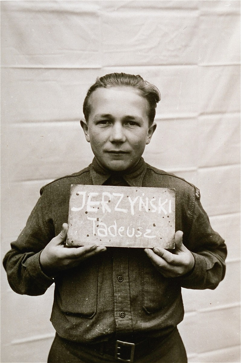 Tadeusz Jerzynski holds a name card intended to help any of his surviving family members locate him at the Kloster Indersdorf DP camp.  This photograph was published in newspapers to facilitate reuniting the family.