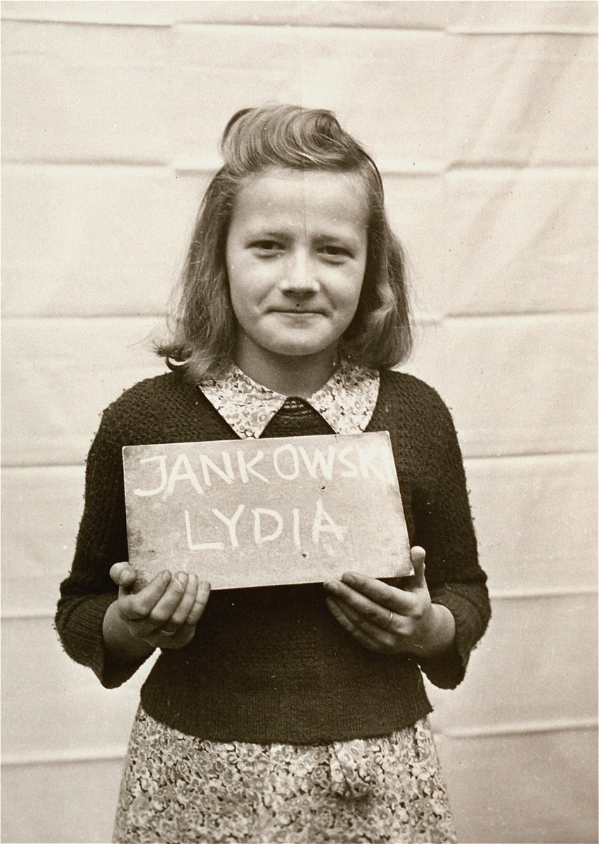 Lydia Jankowski holds a name card intended to help any of her surviving family members locate her at the Kloster Indersdorf DP camp.  This photograph was published in newspapers to facilitate reuniting the family.