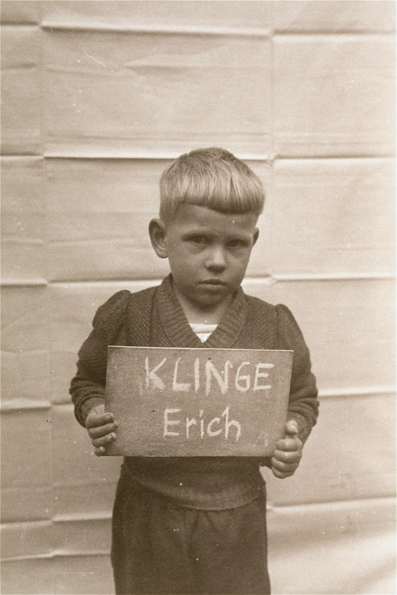 Erich Klinge holds a name card intended to help any of his surviving family members locate him at the Kloster Indersdorf DP camp.  This photograph was published in newspapers to facilitate reuniting the family.