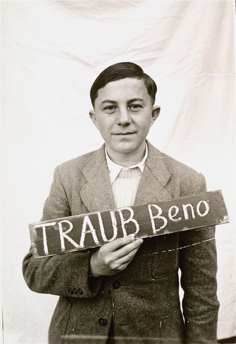 Beno Traub holds a name card intended to help any of his surviving family members locate him at the Kloster Indersdorf DP camp.  This photograph was published in newspapers to facilitate reuniting the family.