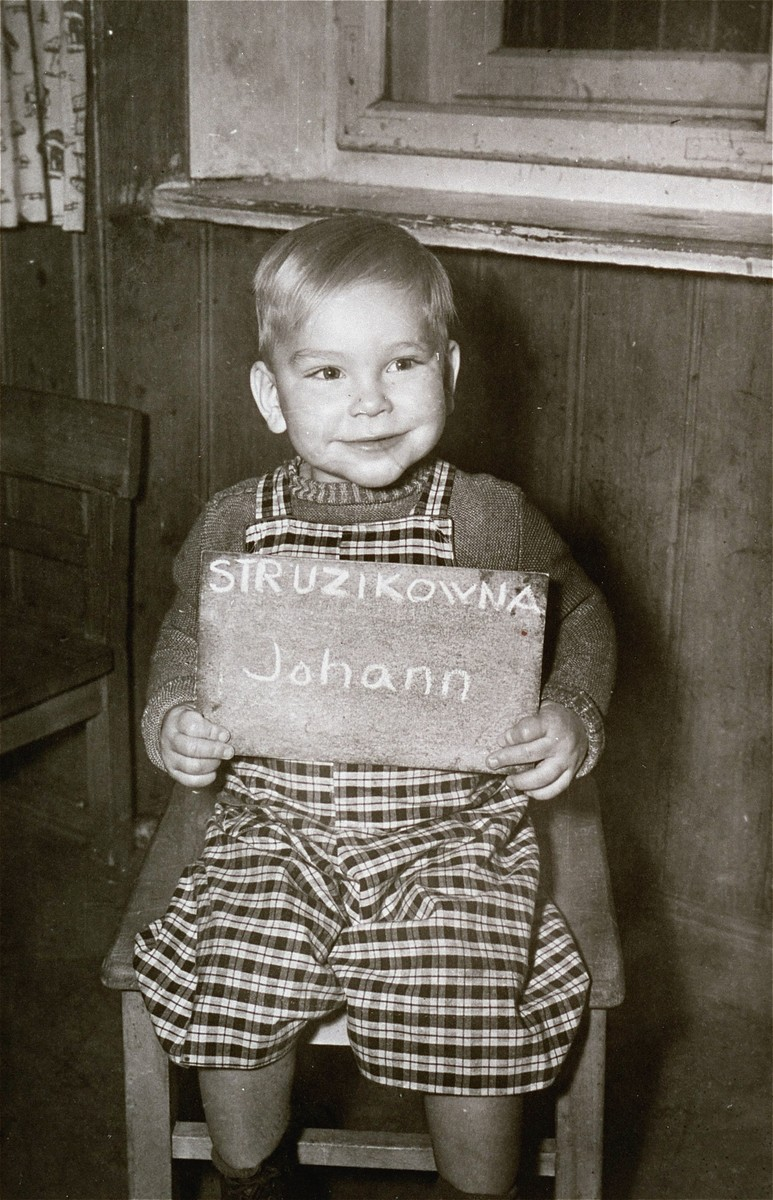 Johann Struzikowna holds a name card intended to help any of his surviving family members locate him at the Kloster Indersdorf DP camp.  This photograph was published in newspapers to facilitate reuniting the family.