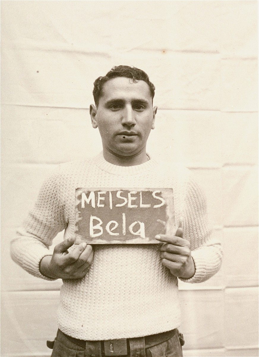 Bela Meisels holds a name card intended to help any of his surviving family members locate him at the Kloster Indersdorf DP camp.  This photograph was published in newspapers to facilitate reuniting the family.